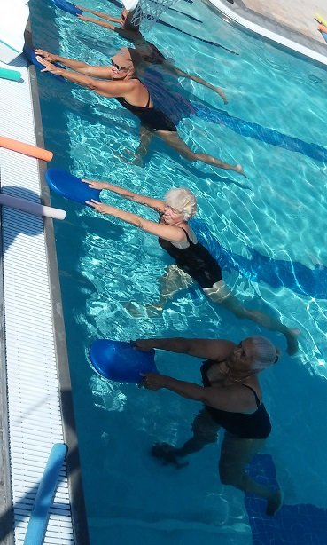 women doing warrior 3 pose with pool kickboards to show the properties of aqua yoga