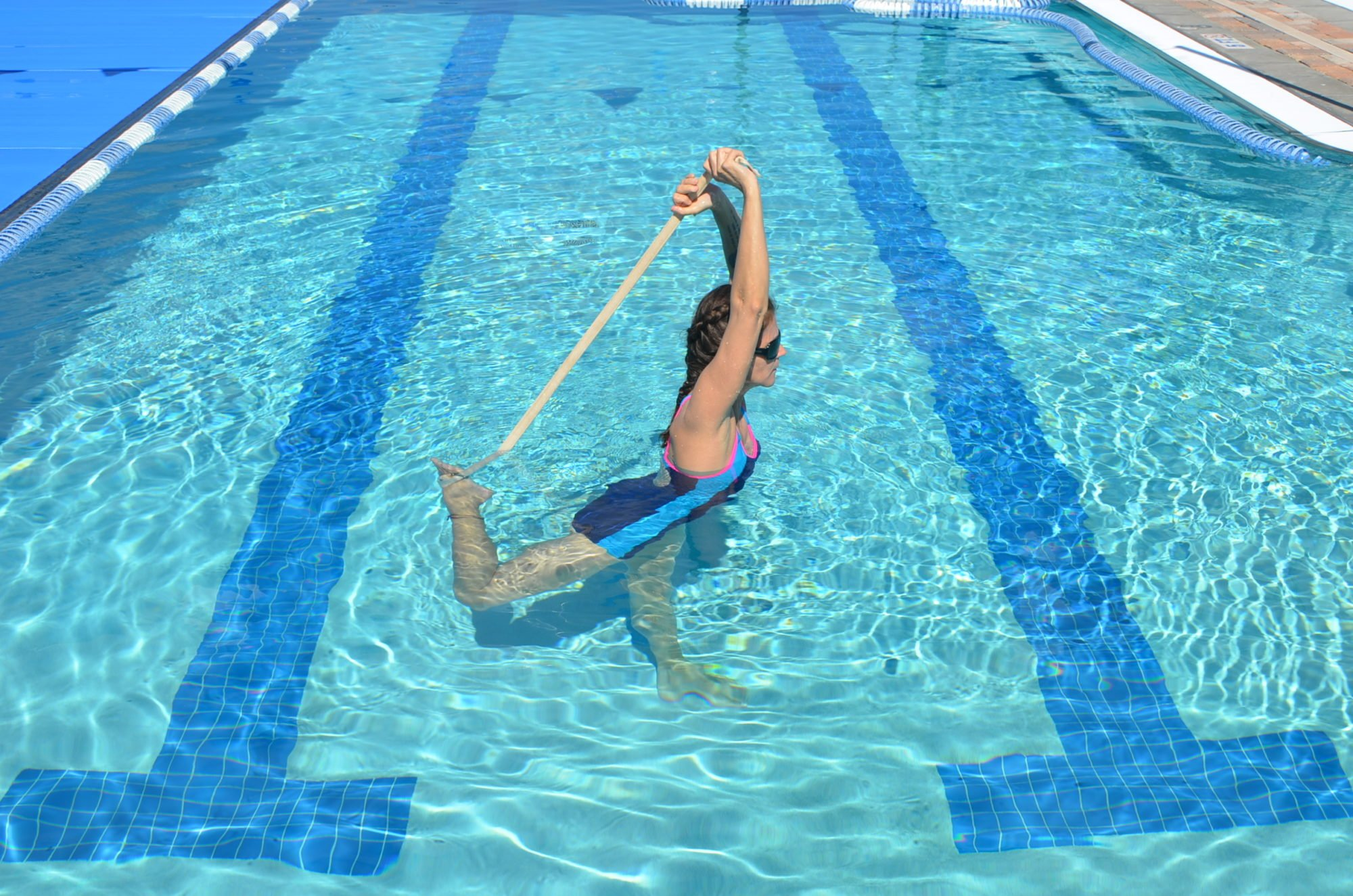 woman doing dancers pose in the pool