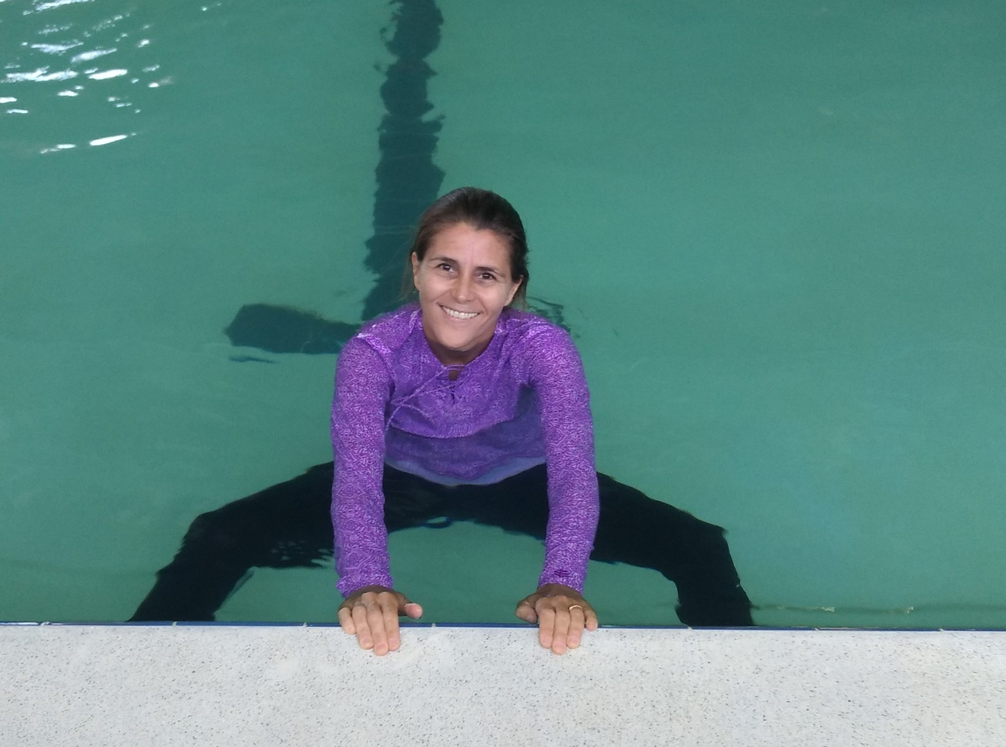 woman doing dead bug pose in the pool