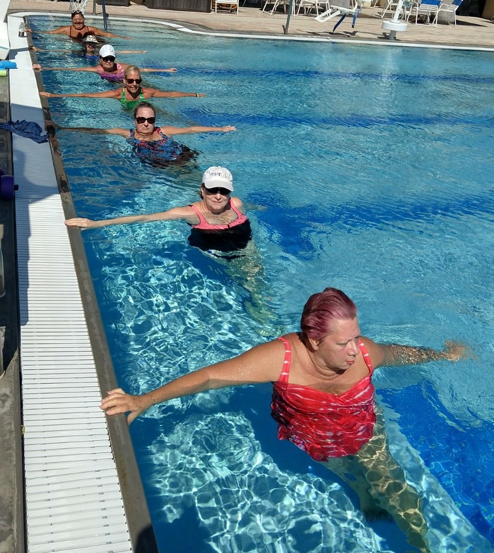 women doing yoga along the pool wall