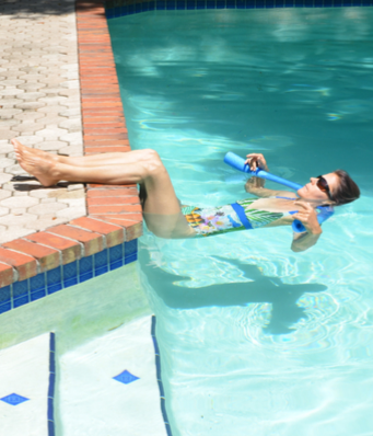 woman doing floating meditation with a pool noodle and the pool wall during aqua yoga
