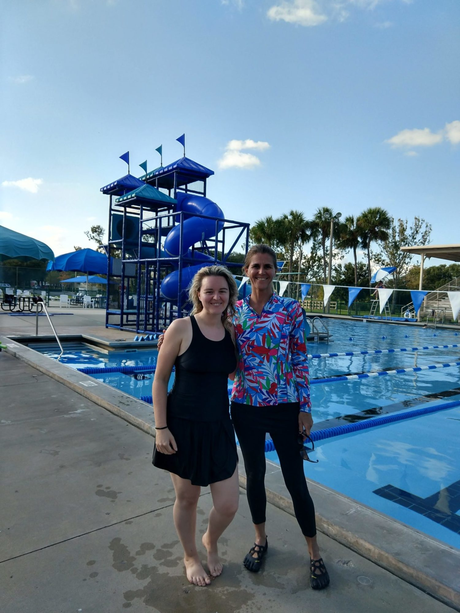 two women standing in front of the pool who are participants in the aqua yoga teacher mentorship