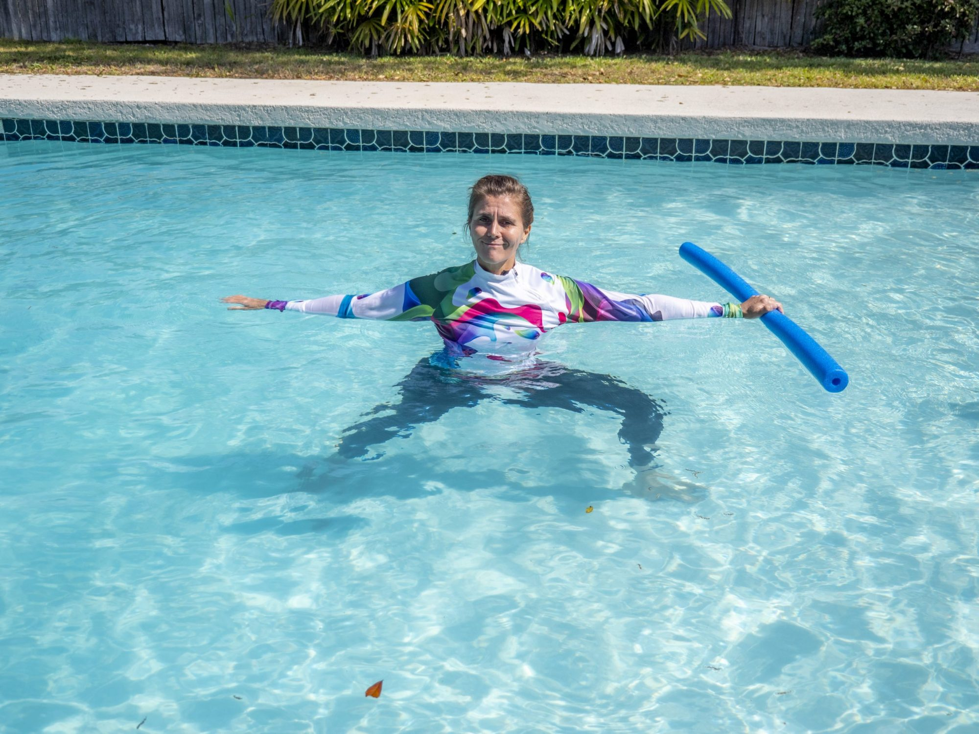 woman doing warrior 2 pose in the pool with a pool noodle as aqua yoga for arthritis