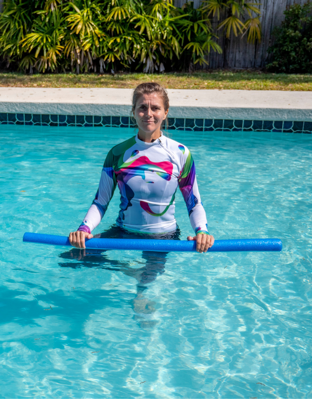 woman doing tree pose with a noodle in the pool to show aqua yoga for arthritis