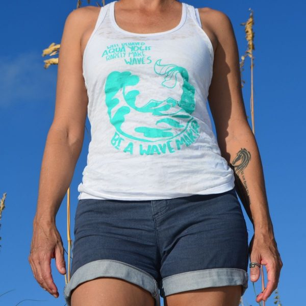 woman standing on the beach wearing an aqua yoga tank top in white who says well behaved aqua yogis rarely make waves, be a wavemaker