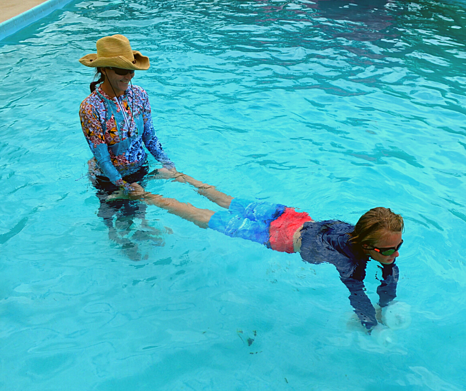 woman holding boy by the feet as he walks on aquatic dumbbells in the pool to show how to have a cheap family pool staycation