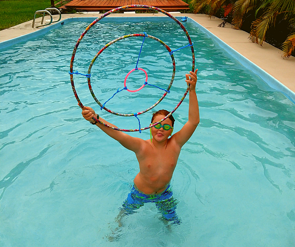 boy holding up a target made of hula hoops while in the pool to show how to have a cheap family pool staycation