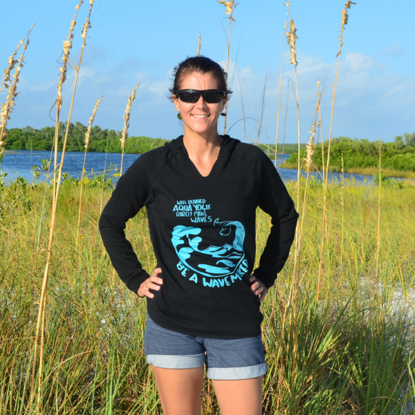 woman standing on a beach in front of seagrass wearing a black aqua yoga sweatshirt