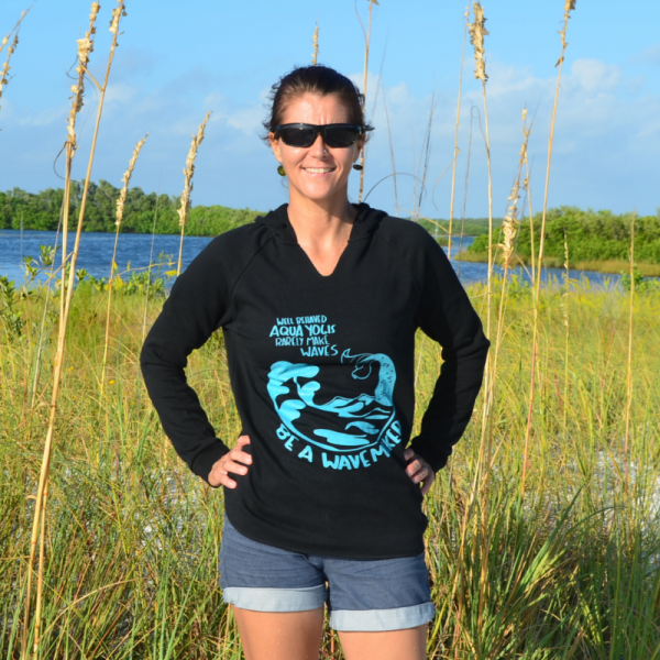 woman on the beach in front of seagrass wearing a black sweatshirt that says well behaved aqua yogis rarely make waves, be a wavemaker