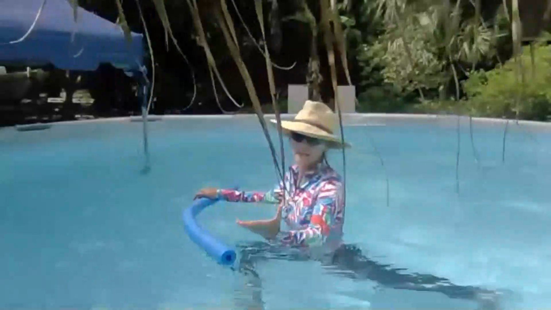woman in the pool with a pool noodle explaining the aqua yoga online course