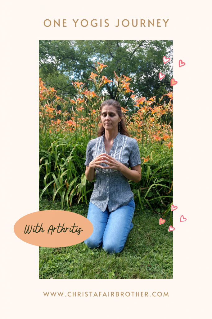 woman kneeling in meditation in front of flowers to show a yogi with arthritis
