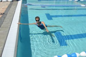 woman in the pool doing side plank using the pool wall with aqua pilates moves like lifting her top leg up and down to show an example of aquatic therapy