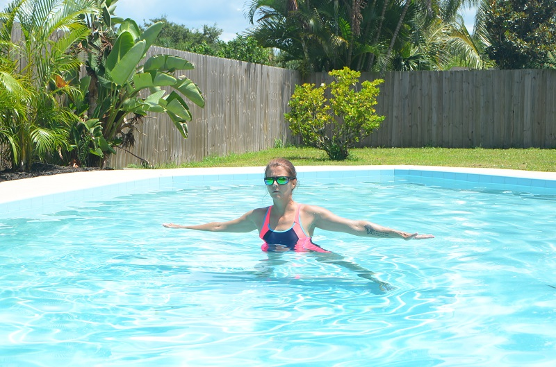 Woman walking sideways in the pool to warm up as part of the aqua yoga challenge