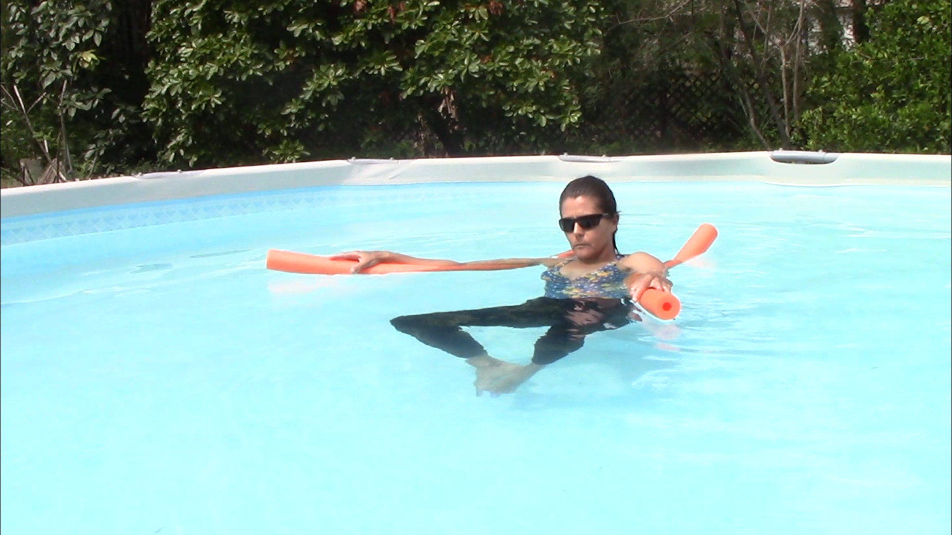 Woman in the pool with two pool noodles