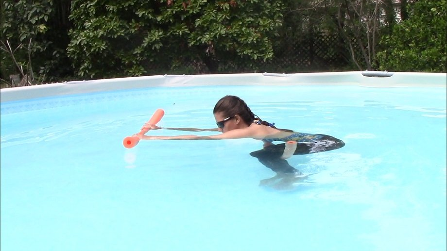 woman doing childs pose in the pool with two pool noodles