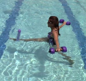 Woman doing a suspended lunge in the pool with a pool noodle under her ankle and an aquatic dumbbell in each hand to show how Burdenko techniques can be used in aquatic therapy
