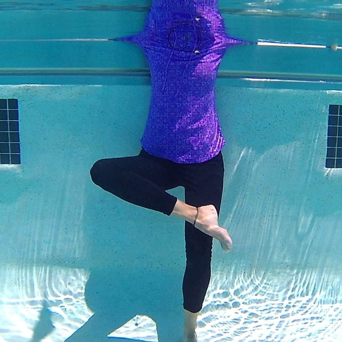 woman doing figure 4 pose in the pool wearing purple to promote aqua yoga for lupus