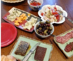 Mezze plate spread with olives, sausage, cheese, and bread to celebrate the finishing of writing a yoga book.