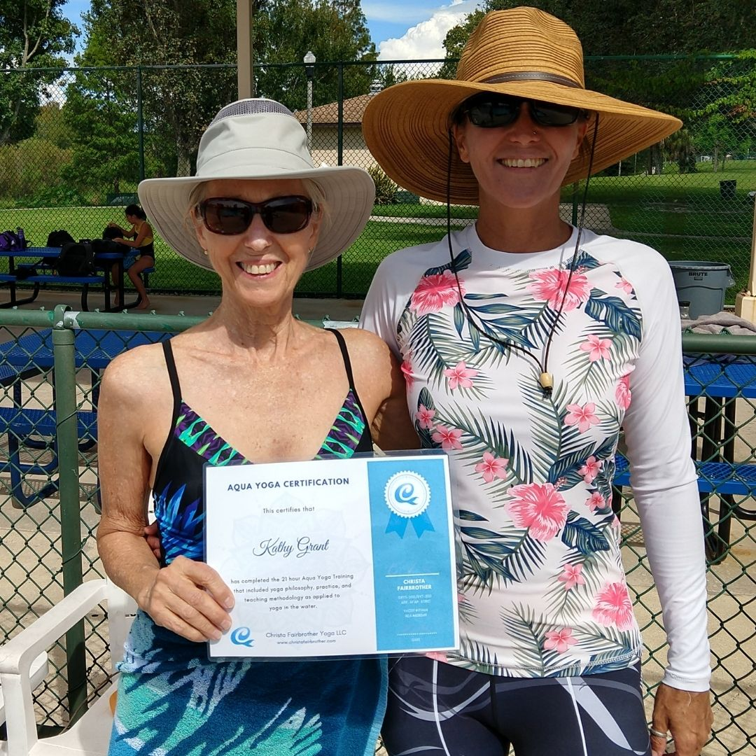 two women standing on the pool deck.  One holds the certificate she earned through the online aqua yoga certification